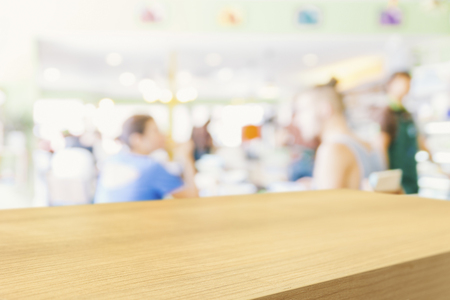 Empty wooden table and blurred people in cafe background, product display montage