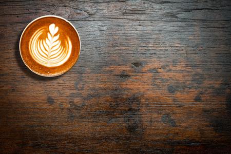 cảnh quan: Ly cà phê nhìn hàng đầu trên nền bảng bằng gỗ tối màu với không gian sao chép