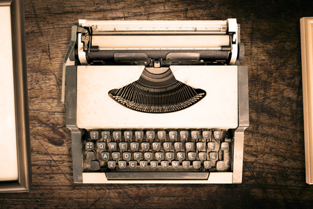 classical mechanics: Top view of vintage typewriter with old frame on wooden texture background. retro style