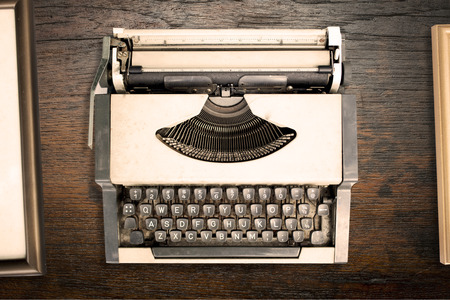 old fashioned sepia: Top view of vintage typewriter with old frame on wooden texture background. retro style