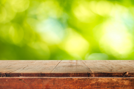 Empty wooden table and green natural spring blur bokeh background , product display montage Standard-Bild