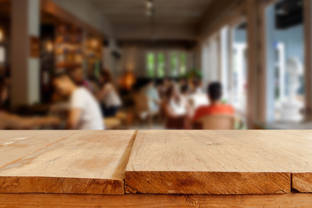 empty of people: Empty wooden table and blurred people in cafe background, product display montage