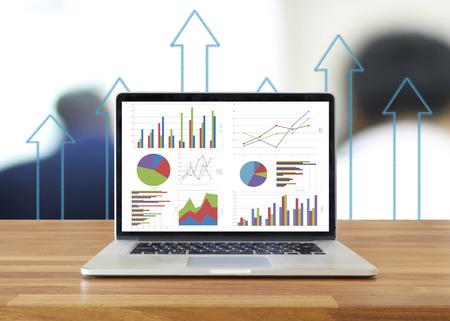 contabilidad: Computadora port�til en la mesa de madera que muestran los cuadros y gr�ficos, an�lisis de negocio de Contabilidad, Estad�stica Concept.