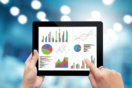 graph: Closeup hand holding digital tablet show analyzing graph,planing,business success