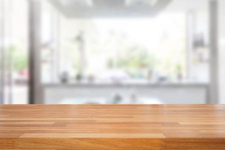 decoracion mesas: mesa de madera vac�a y el fondo de la cocina borrosa, montaje de productos de visualizaci�n Foto de archivo