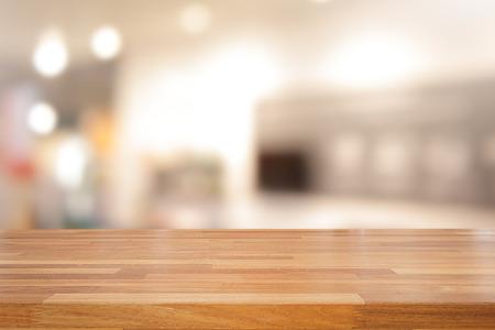 Tavola di legno vuota e fondo interno, esposizione del prodotto, negozio vago con bokeh