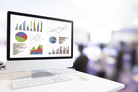 Moderne Computer mit Tastatur und Maus auf dem Tisch Diagramme und Graphen gegen verschwommen Geschäftsleute Hintergrund zeigt, Analysis Geschäft, Statistik-Konzept.