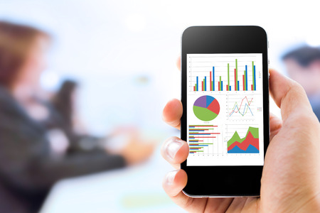 grafica de barras: Primer plano de mano que sostiene el teléfono móvil con el análisis gráfico de las personas en la conferencia de negocios y de fondo de la presentación