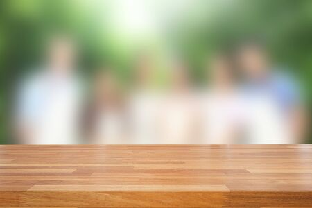 empty of people: Empty wooden table against group of people with tree background, product display montage Stock Photo