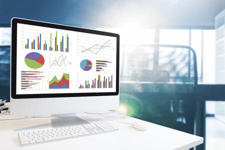 estadisticas: moderno del ordenador con teclado y ratón en la mesa mostrando los cuadros y gráficos contra el fondo de la oficina en tono azul, análisis de negocios, Concepto Estadísticas.