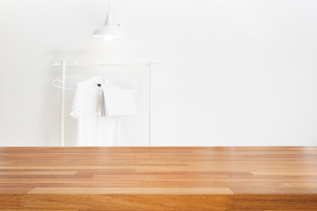 Empty wooden table and modern white clean room background with shirt hanging, lamp, book,  Ready for product montage