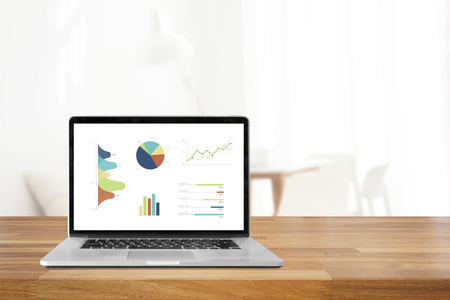 Laptop on wooden table showing charts and graph against office background ,Analysis Business Accounting, Statistics Concept.