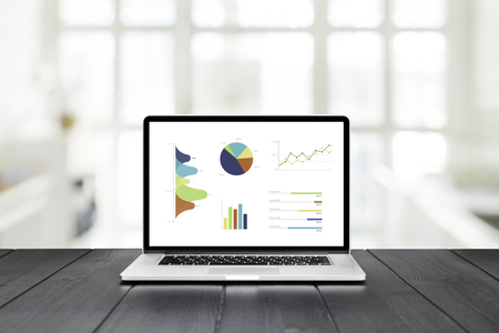 Laptop on wooden table showing charts and graph against white office room and windows background ,Analysis Business Accounting, Statistics Concept.