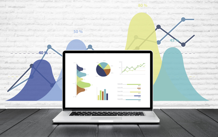 Laptop on wooden table showing charts and graph colorful graphics, Analysis Business Accounting, Statistics Concept.