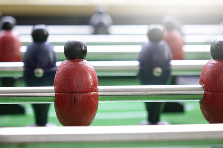 Background of foosball table soccer, inred color, football table in depth of field. Standard-Bild - 110441636