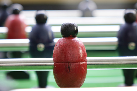 Background of foosball table soccer, inred color, football table in depth of field. Standard-Bild - 110441638