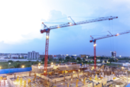 Blurred backgrounf of construction site with cranes working on a building light complex, with blue sky, sunset,twilight time of day Standard-Bild - 111989987