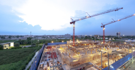 Blurred backgrounf of construction site with cranes working on a building light complex, with blue sky, sunset,twilight time of day Standard-Bild - 111989988