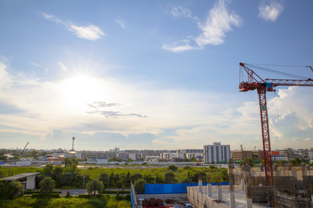 Large construction site with cranes working on a building complex, with clear blue sky and the sun, daylight Standard-Bild - 111990117