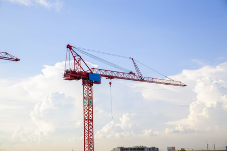 Large construction site with cranes working on a building complex, with clear blue sky and the sun, daylight Standard-Bild - 111990118