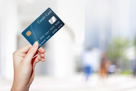 female hand holding credit card against blur outdoor shopping mall background Standard-Bild - 138424751