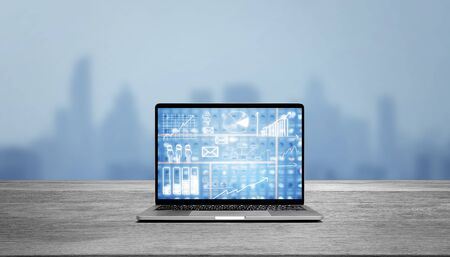 Modern laptop on wood table showing charts and graph against blue business building background Standard-Bild - 136286462