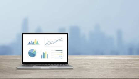 Modern laptop on wood table showing charts and graph against blue business building background Standard-Bild - 136286449