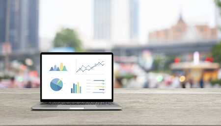 Modern laptop on wood table showing charts and graph against blue business building background Standard-Bild - 136286374