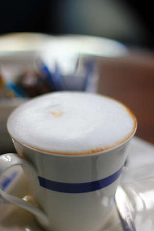 White coffee cup on cloth texture of coffee photo