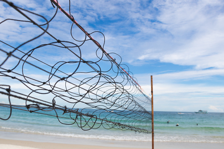 Old beach volleyball net with cloudy sky at Koh Samet, Rayong province, Thailand Stock Photo