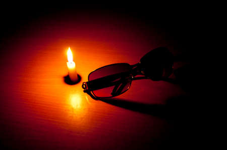 blindness: Single Candle on table with sunglass in front depicting blindness as a theme