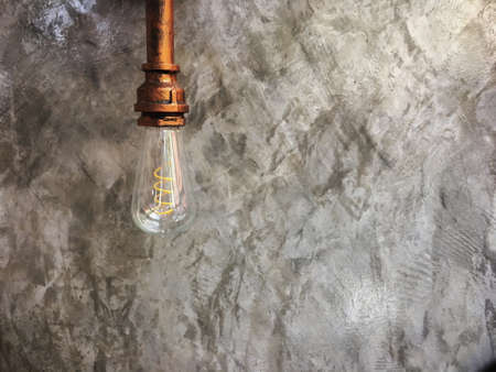 Vintage lighting lamp hang in front of cement wall at loft Imagens