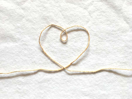 Heart shape made from hemp rope on softness cotton white background. A concept of love. Stock Photo