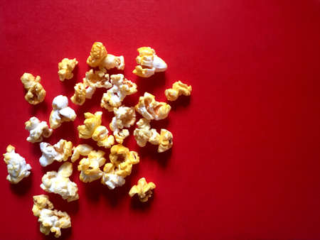 Popcorn with cheese and butter flavor on red background.