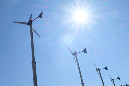 Wind turbine on blue sky background in the afternoon. Windmill for electricity generating. Imagens