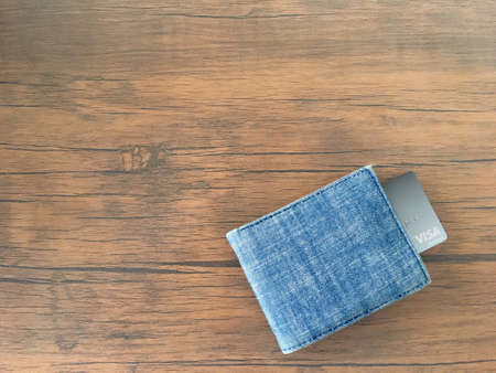 Visa card in blue jeans wallet on brown wooden table background.