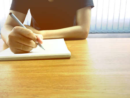 Young businessman holding the pen and hand writing on notebook in office. Imagens