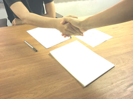 Two business people hand shaking at workplace for business cooperation with deal concept.