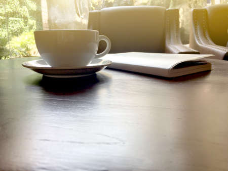Afternoon tea in white cup with notebook on brown wooden table in the cafe.