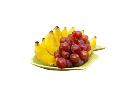 Red grape and banana decoration on dish isolated on white background Imagens