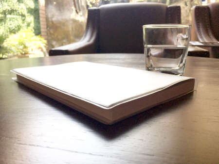 Mineral drink water in transparent glass with notebook on brown wooden table in the cafe.