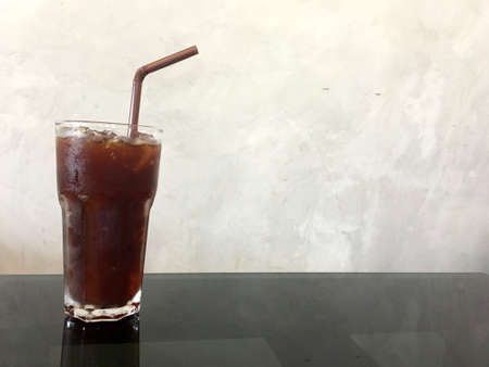 Ice black coffee in transparent glass with brown tube on glass table in the cafe