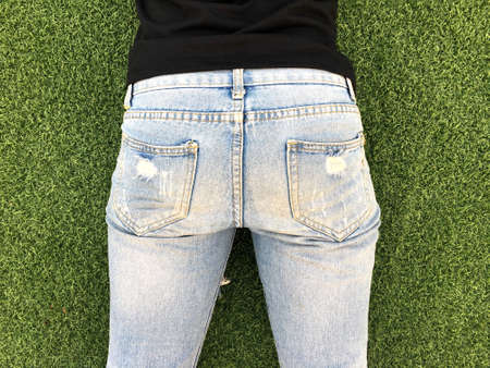 Young woman bottom in tight light blue jeans in front of green grass background. Stock fotó