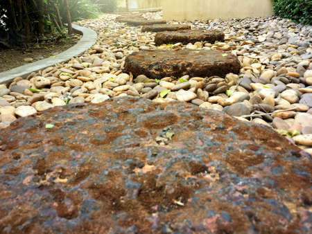 Red brick stone footpath step with low angle view on small rock in the garden.