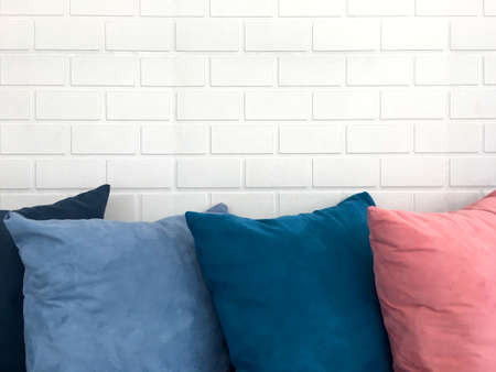 Colorful decorative resting pillow stack on sofa in front of white brick background.