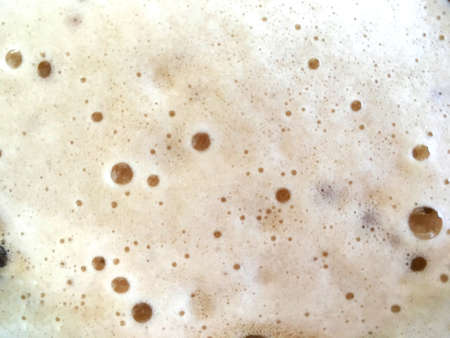 Carbonated drink foam close up with small bubbles texture