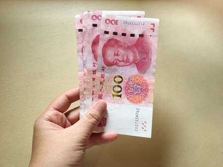 Woman hand holding one hundred Chinese yuan money on yellow background. Chinese banknotes.