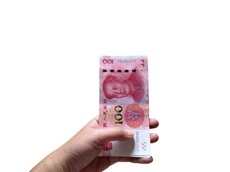 Woman hand holding one hundred Chinese yuan money stacking isolated on white background. Chinese banknotes. Banco de Imagens