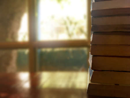 Old book stacking on wooden table in front of window at library room. Business and education concept.