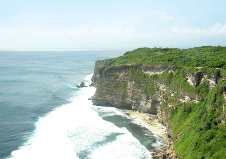 The nature high cliff with green plant reach to deep blue sea and surf on the coast under clear sky.